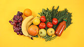 Healthy organic food on a yellow table, healthy lifestyle concept. Vegetables, fruits, grapes, herbs, bananas, citrus fruits, diet ingredients, flat lay, place for text