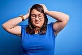 Beautiful brunette plus size woman wearing casual t-shirt over isolated blue background suffering from headache desperate and stressed because pain and migraine. Hands on head.