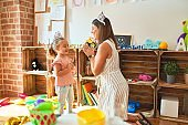 Beautiful teacher and blond student toddler girl playing to be a princess wearing crown at kindergarten