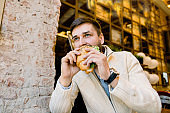 Side angle view of young handsome hungry man eating croissant while sitting in outdoor cafe. Portrait of handsome young Caucasian man eating delicious croissant