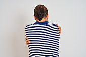 Young man wearing casual striped polo standing over isolated white background Hugging oneself happy and positive from backwards. Self love and self care