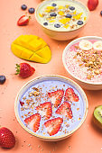 Vegetarian healthy food made from multi-colored smoothies with matches and berries on a bright pink background.