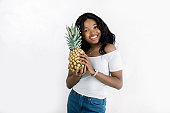 Cheerful attractive african american young woman in jeans and white t-shirt standing and holding pineapple over white background. Beautiful African-American woman with pineapple. Copy space