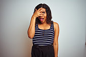 Transsexual transgender woman wearing striped t-shirt over isolated white background peeking in shock covering face and eyes with hand, looking through fingers with embarrassed expression.