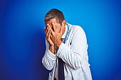 Handsome middle age doctor man wearing stethoscope over isolated blue background with sad expression covering face with hands while crying. Depression concept.