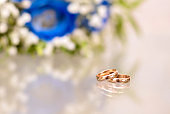 Gold wedding rings next to the bride's bouquet