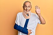 Handsome mature senior man wearing cervical collar and arm on sling waiving saying hello happy and smiling, friendly welcome gesture