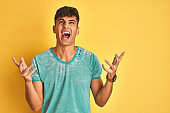 Young indian man wearing green t-shirt standing over isolated yellow background crazy and mad shouting and yelling with aggressive expression and arms raised. Frustration concept.