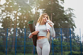 Portrait of a woman in fitness wear relaxing after hard workout standing outdoors with a yoga mat, drinking water from a bottle and looking away. Sport and healthy lifestyle concept. Fitness outdoors