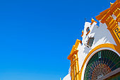 Upper decorative part of architectural building in white and yellow colors, clear blue sky. Seville, Spain