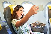 Young traveller woman sitting inside plane at the airport with sky view from the window taking a selfie with smartphone