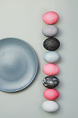 Line of colorful Easter eggs near blue plate on grey background