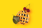 Cherry mini pie with ripe cherries on a bright yellow background