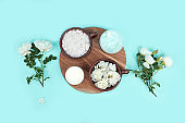 Spa and wellness composition with rose flower aroma water in wooden bowl, rose water aromatherapy and body cream, flat lay, lifestyle concept,