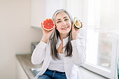 Healthy eating for senior people, vegan food concept. Attractive smiling Caucasian elderly woman sits on the countertop in modern kitchen, holds in hands fresh avocado and grapefruit