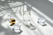 Cosmetic bottle of essence with a dropper and ice on a background of beautiful palm shadows