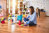 Young caucasian child playing at playschool with teacher. Mother and son at playroom with intelligence toy