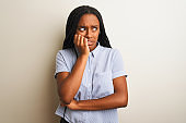 Young african american woman wearing striped shirt standing over isolated white background looking stressed and nervous with hands on mouth biting nails. Anxiety problem.