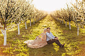Enjoying time together. Beautiful young loving wedding couple in elegant wear sitting back to back on the green grass and looking away with smile, rows and alleys of flowering fruit trees around