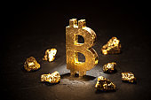 Gold sign bitcoin and gold nuggets on black background