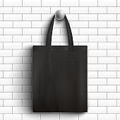 Black fabric tote bag hanging on white brick wall - realistic branding mockup