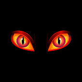 Glowing red evil monster eyes on black background - scary Halloween element