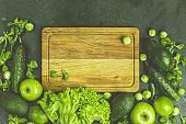 Fresh organic green vegetables and fruits on green background. Spring diet, healthy raw vegetarian, vegan concept, detox breakfast, alkaline clean eating