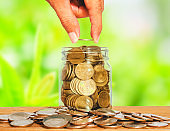 investor business man hand putting coins in jar on wood table with blur nature park background. money saving concept for financial banking and accounting.