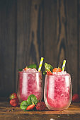 Strawberry drink with ice. Two glass of strawberry ice drink with ripe berry on wooden turquoise table surface. Alcoholic nonalcoholic summer fresh drink beverage.