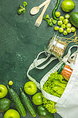Zero waste concept. Eco-friendly shopping, flat lay. Fresh organic green vegetables and fruits on green background. Spring diet, healthy raw vegetarian, vegan concept, alkaline clean eating