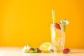 Glasses of cold icy refreshing drink with lemon and strawberry. Bright yellow background. Fresh cocktail drinks with ice fruit, herb and chamomile decoration