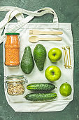 Zero waste concept. Eco-friendly shopping, flat lay. Fresh organic green vegetables and fruits on gray background. Spring diet, healthy raw vegetarian, vegan concept, alkaline clean eating