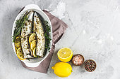 Mackerels served on white dish with lemon, thyme, rosemary and spices. Raw marinated fishes on light gray surface. Seafood background