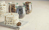 American puffed rice cakes. Healthy snacks with almonds, raisins, peanuts, pistachios in glass jars on light pink concrete surface.