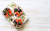 Open sandwiches with cream cheese, strawberries, blueberries, jam and almond flakes