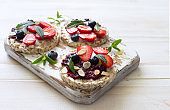 Open sandwiches with cream cheese, strawberries, blueberries, jam and almond flakes close up