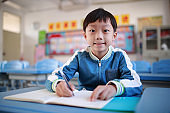 asian elementary schoolboy thinking while doing homework in classroom