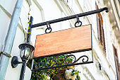 Empty wooden sign with wrought-iron frame and vintage street lamp hangs on the wall of house outside. Blank for advertising or signage of store, cafe, or public organization