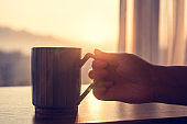 Hand holding cup of drink with sunlight