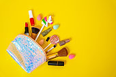 Womens set of cosmetics, brushes for powder and blush, sponges for foundation, lipstick, nail polishes, bottle of perfume scattered from cosmetic bag on yellow background, top view, copy space.