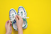 Human hands tie shoelaces on stylish sneakers decorated with shiny lines on yellow background, top view, copy space for lettering. Studio shot for new shoe advertising banner