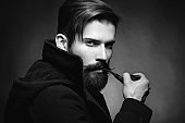 Brutal man with a beard Smoking a pipe