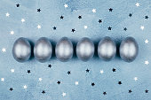 Silver colored Easter eggs and stars on blue textured background.