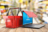 Laptop and shopping cart on table and shop interior in background - 3d illustration