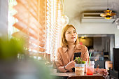 Happy young asian women using smart phone while sitting in cafe