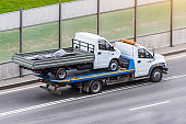 A truck is transporting another small truck on the road.