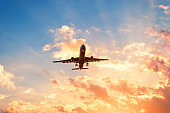 Travel by plane in a beautiful sky at sunset with clouds.