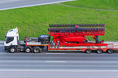 Transportation of large agro-complex machines for cultivating and sowing crops on long trailers by trucks along the highway in the city.