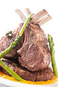 Close up picture of a roasted rack of lamb chop and vegetables on white background