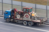 Transportation of small agricultural tractor in the back of a truck.
